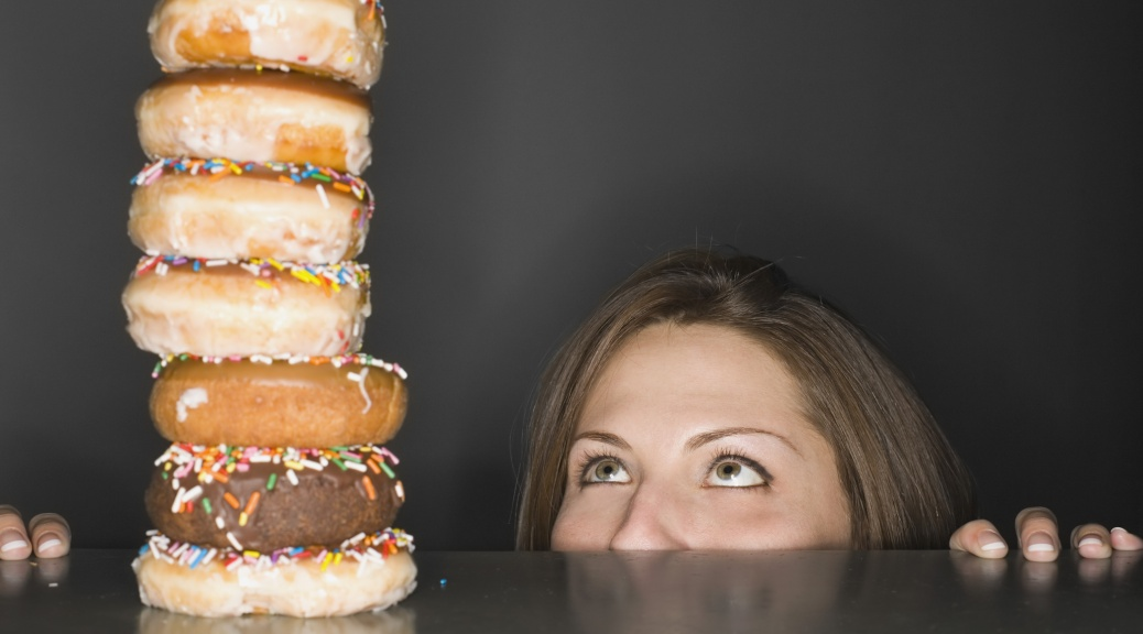 Woman looking at stack of donuts in awe